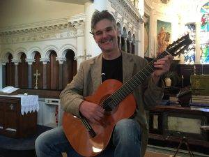 Darren looking smug on a seven string classical guitar rehearsing for a concert