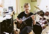 Darren playing guitar sat down in recording studio.